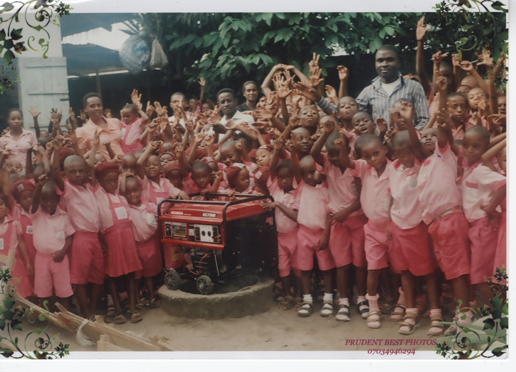 Some of our students in Bodo posing with a new portable generator we purchased for the school to help run its borehole for improved drinking water.